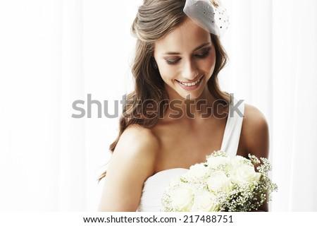 Young bride in wedding dress holding bouquet, studio shot   Foto stock ©