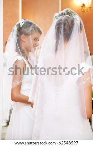 Young bride looking at the mirror.