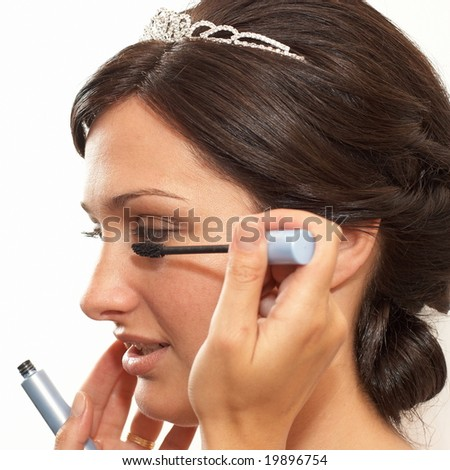 Young bride making her makeup for wedding ceremony