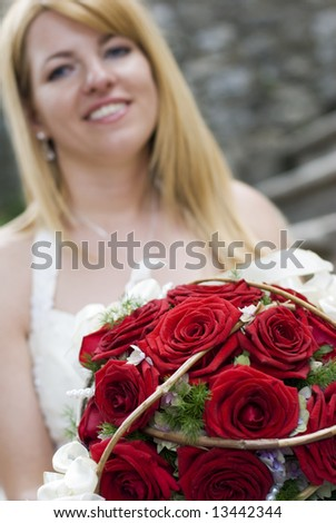 young bride with bouquet of red roses