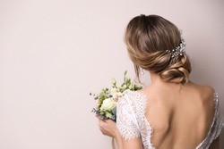 Young bride with elegant hairstyle holding wedding bouquet on beige background, back view. Space for text