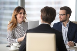 Young broker businesswoman talking to business partners. Woman consulting, giving instructions, explaining terms of contract. Man in glasses looking colleague and listening.