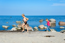 Young brother and sister running on the beach alongside the ocean and small rocks as they enjoy their summer vacation on the beach