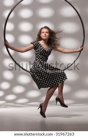 Young brown-haired woman sitting on the metal ring - stock photo