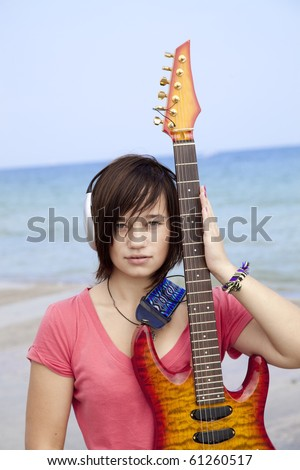 Young brunet girl with headphone and guitar on the beach.
