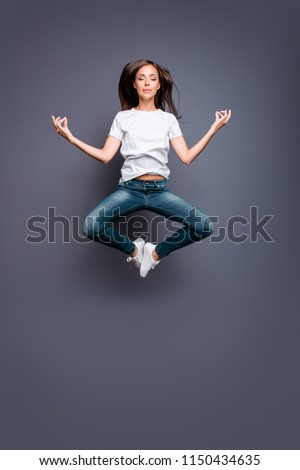 Young brunett female practicing yoga levitate at the air. Calm girl jumping up in a position of meditation isolated on gray background #1150434635