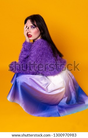 Young brunett woman with colorful makeup in purple sweater sat down covers one eye wirh hand. Studio foto #1300970983
