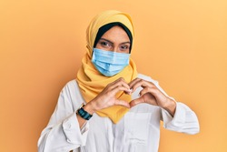 Young brunette arab woman wearing traditional islamic hijab and medical mask smiling in love showing heart symbol and shape with hands. romantic concept.