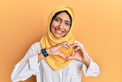 Young brunette arab woman wearing traditional islamic hijab scarf smiling in love doing heart symbol shape with hands. romantic concept.