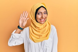 Young brunette arab woman wearing traditional islamic hijab scarf waiving saying hello happy and smiling, friendly welcome gesture