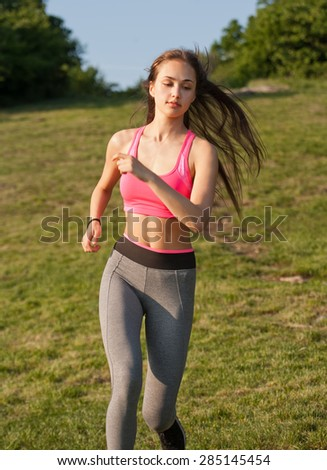 Young brunette beauty enjoying outdoors exercise in nature.