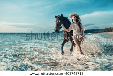Young brunette beauty having fun with horse on the beach