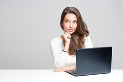 Young brunette beauty with a black laptop computer.