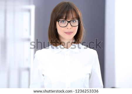 Young brunette business woman looks like a student girl working in office. Caucasian  girl standing straight #1236253336