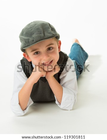 Young brunette caucasian boy laying on stomach with flat cap