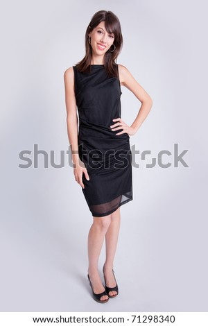 Young brunette dressed up in a little black dress and high heels