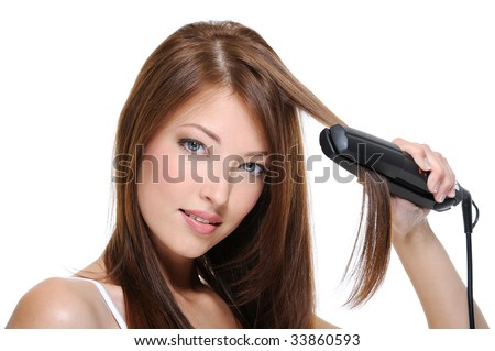 young brunette girl doing hairstyle with flat iron - isolated on white