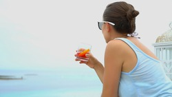 Young brunette girl drinking red cocktail from a glass on outdoor terrace by the sea