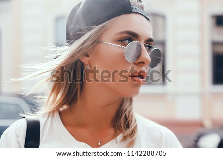Stock Photo Young brunette girl in black standing outside and watching the sunset in the city, the sun shines brightly, fashionable clothes on a girl, hipster style,, tattoo, street photo, mood, freedom