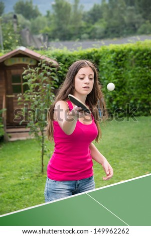 young brunette girl plays table tennis outdoors