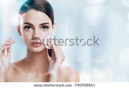 Young brunette girl removing makeup from her face. Photo of beautiful girl with cotton pads  on shiny silver background. Skin care and beauty concept. Copy space