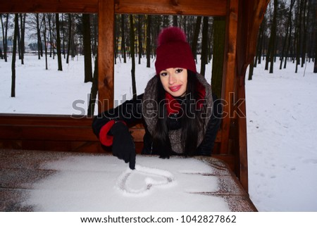 Young brunette girl sitting at a snowy table draws a heart on white snow