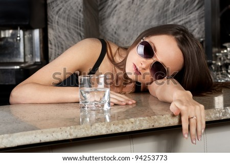 Young brunette girl with a glass of vodka