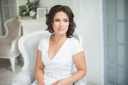 young brunette girl with curly hair in a white dress sits in a beautiful armchair, looks out the window. Beautiful brown eyes. Mother's Day, Women's Day. Birthday. Close-up