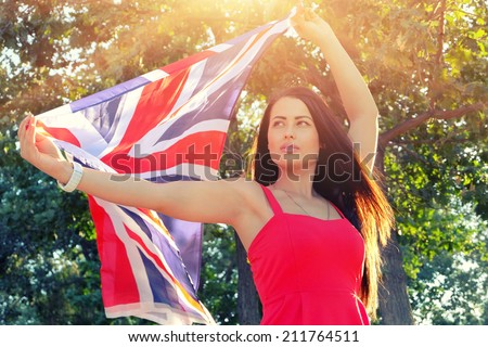 Young brunette holding UK flag in her outstretched hands, flag fly by the wind