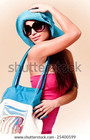 young brunette in pink summer dress, wearing hat, sunglasses and beach bag