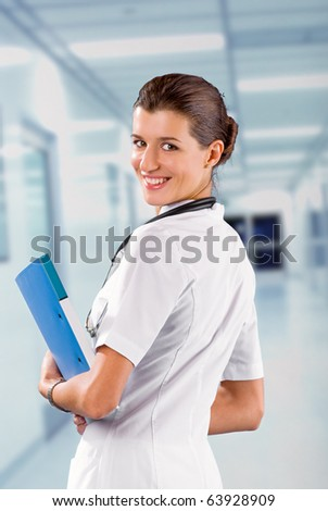 young  brunette in white medical gown and a stethoscope and file folder in an hospital