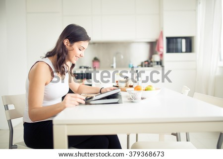 Young brunette is reading the newspaper while having breakfast at home.Modern woman lifestyle-healthy fitness breakfast,coffee and fruit,reading motivational quotes.Starting your day,positive energy #379368673