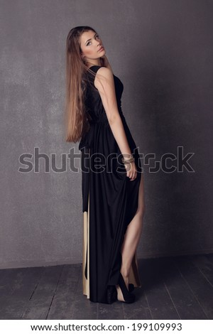 Young brunette lady in black ang golden dress posing on grey background. Fashion studio shot of beautiful woman with makeup and hairstyle wearing evening dress #199109993