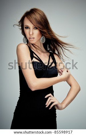 Young brunette lady in black dress posing on grey background - stock photo