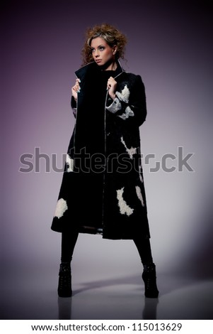 Young brunette lady in wool coat posing on purple background