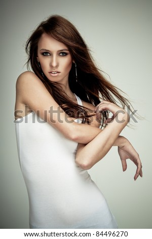 Young brunette lady posing on grey background