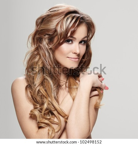 Young brunette lady with a beautiful hair on gray background