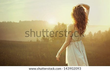 Young brunette looking at sunrise
