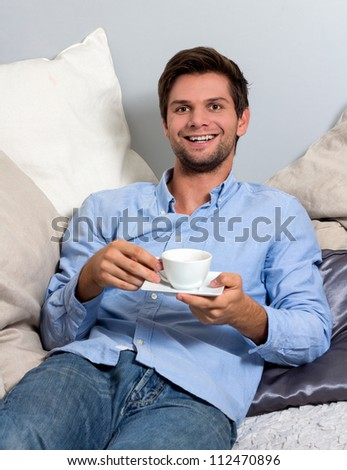Young brunette man in blue clothing  enjoying a coffee break