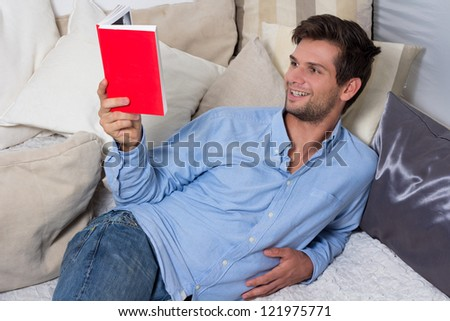 Young Brunette Man in Blue Shirt Reading A Book