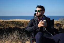 Young brunette man in sunglasses and waterproof jacket holding iron mug cup of coffee,sitting alone on camping chair on cliff by the sea,enjoying vacation in nature landscape.Travel, active lifestyle