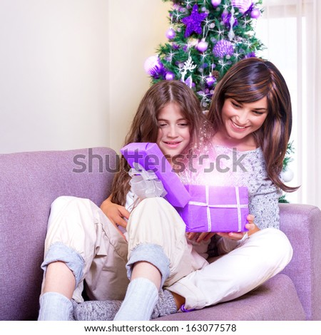 Young brunette mother with teen girl opening Christmas present, excited faces, magical glowing light from gift box, happiness concept