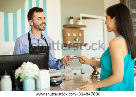 Young brunette paying with a credit card at the cash register in a cake shop