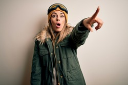 Young brunette skier woman wearing snow clothes and ski goggles over white background Pointing with finger surprised ahead, open mouth amazed expression, something on the front