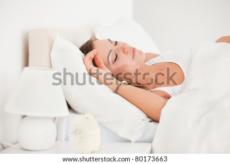 Young brunette sleeping in her bed against a white background - stock photo