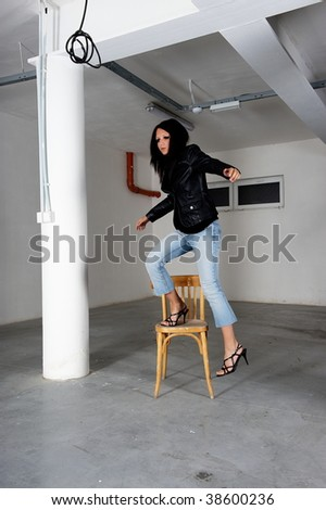 Young brunette standing on a old chair in basement garage
