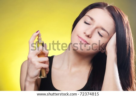 Young brunette woman applying perfume on her body