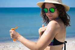 Young brunette woman applying suntan solar cream to her shoulder from a plastic container, wearing sunglasses and summer hat with ocean in background, Sunscreen spf lotion. Copy space.