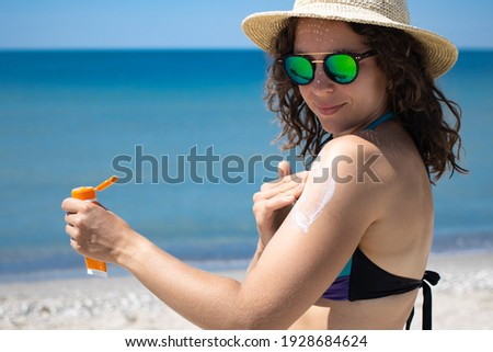 Young brunette woman applying suntan solar cream to her shoulder from a plastic container, wearing sunglasses and summer hat with ocean in background, Sunscreen spf lotion. Copy space. Stock photo ©
