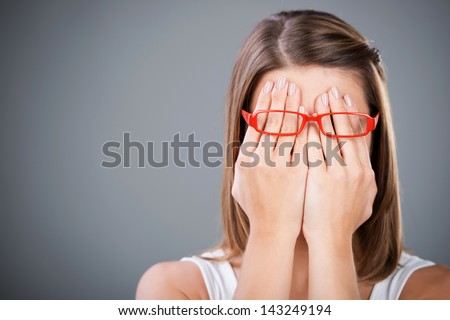 Young brunette woman covering face using her both hands